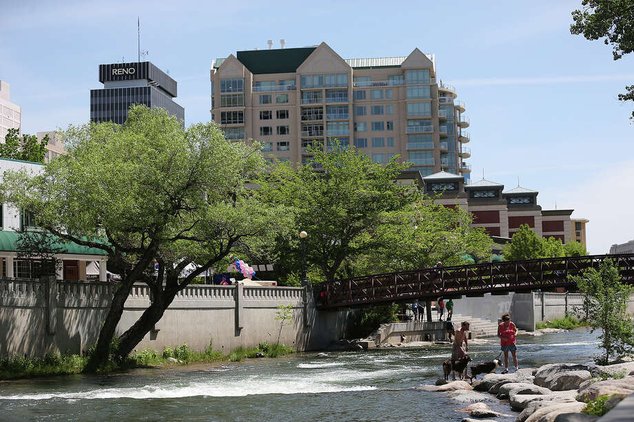People play by the Truckee River in the Riverwalk District of downtown Reno, Nevada, May 17, 2014. The area was redeveloped in the mid-1990Õs and is home to restaurants, bars, theaters and museums. Local leaders are trying to lure people into making downtown their residence. It is made up of mostly casinos and hotels. Reno is in competition with Texas along with three other states for a $5 billion Tesla Gigafactory. It will produce lithium batteries for its vehicles. Tesla is expected to announce and break ground at a site in early June. The factory is expected to employ 6,000. Photo: Jerry Lara, San Antonio Express-News / ©2014 San Antonio Express-News