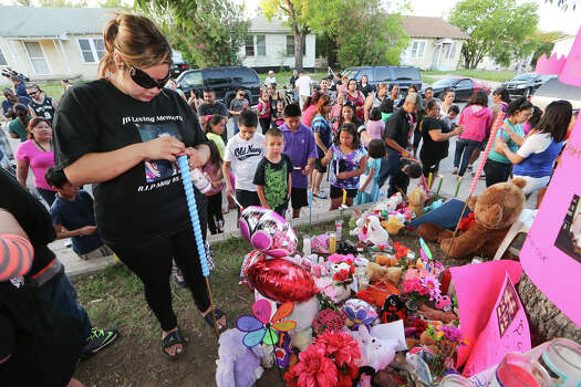 Jennifer DonJuan (left), mother of six-year-old Jennilynn Montana, lights a candle beside a makeshift memorial during a candellight vigil for her daughter at 1444 Aransas on Tuesday, May 20, 2014.  Jennilynn was a victiim of an accidental shooting at the residence on Sunday, MARVIN PFEIFFER/ mpfeiffer@express-news.net Photo: MARVIN PFEIFFER, Marvin Pfeiffer/ EN Communities / Express-News 2014