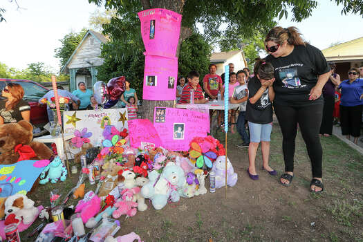 Jennifer DonJuan (right), consoles her eight-year-old daughter Jenabell Montana beside a makeshift memorial during a candellight vigil for her other daughter, six-year-old Jennilynn Montana, at 1444 Aransas on Tuesday, May 20, 2014.  Jennilynn was a victiim of an accidental shooting at the residence the previous Sunday.   MARVIN PFEIFFER/ mpfeiffer@express-news.net Photo: MARVIN PFEIFFER, Marvin Pfeiffer/ EN Communities / Express-News 2014