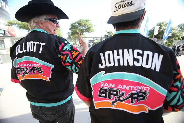Joe Calvey (left) with his son Joey Calvey show up with authentic warmup jerseys from Sean Elliott and Avery Johnson as Spurs fans start to party before the opener against the Thunder at the AT&T Center on May 19, 2014.