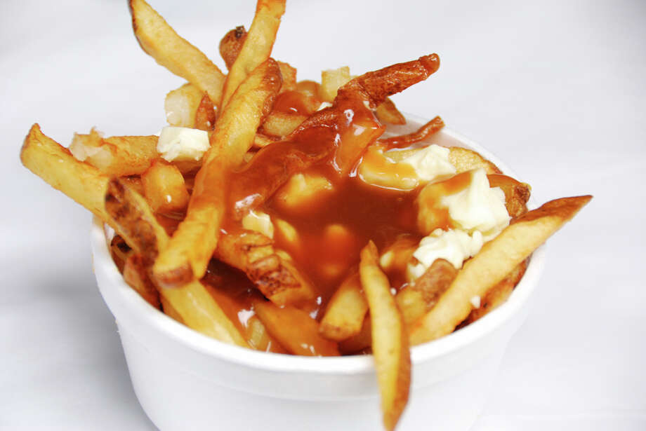 poutine (n., 1982): chiefly Canada: a dish of French fries covered with brown gravy and cheese curds Photo: Lora Clark, Getty Images / (c) Lora Clark