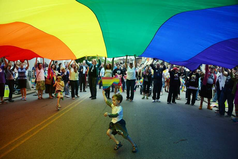 Elijah Socie, 6, of the Brookline section of Pittsburgh , runs underneath a large pride banner while carrying a pride flag to celebrate a federal judge ruling Pennsylvania's ban on same-sex marriage unconstitutional held on Ellsworth Avenue in Pittsburgh, Pa., on Tuesday, May 20, 2014.  (AP Photo/Pittsburgh Post-Gazette, Michael Henninger)  MAGS OUT; NO SALES; MONESSEN OUT; KITTANNING OUT; CONNELLSVILLE OUT; GREENSBURG OUT; TARENTUM OUT; NORTH HILLS NEWS RECORD OUT; BUTLER OUT Photo: Michael Henninger, Associated Press