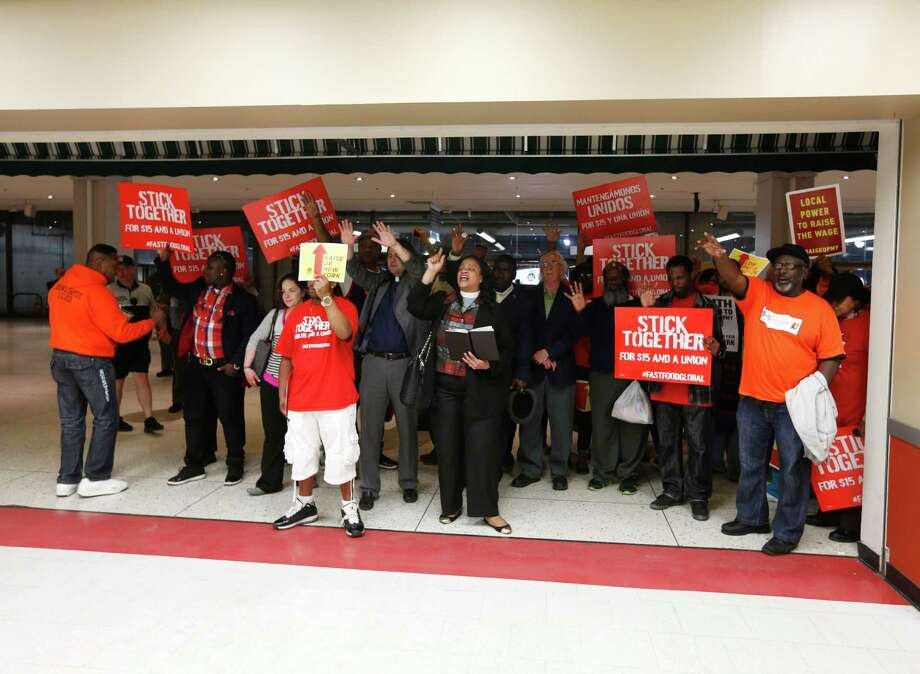 A group rallies outside a McDonald's restaurant at the Empire State Plaza concourse on Tuesday, May 20, 2014, in Albany, N.Y. Fast food workers from around New York state are urging lawmakers to let cities and towns set their own minimum wages. (AP Photo/Mike Groll) ORG XMIT: NYMG108 Photo: Mike Groll / AP