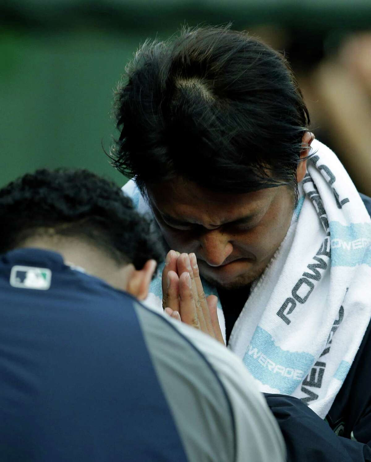 Seattle Mariners' Felix Hernandez, left, and Hisashi Iwakuma, bow to each other in the dugout before their baseball game against the Texas Rangers, Tuesday, May 20, 2014, in Arlington, Texas. (AP Photo/Tony Gutierrez )