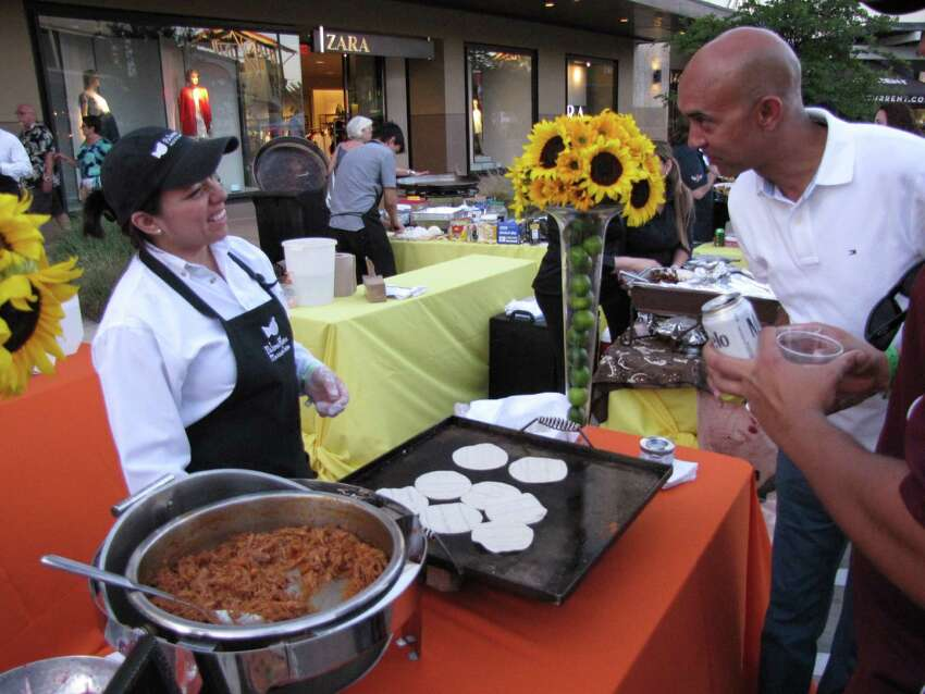 Ana Bragagnini with Paloma Blanca Mexican Cuisine talks with a patron during the Culinaria Best of Mexico event May 16 at The Shops at La Cantera.