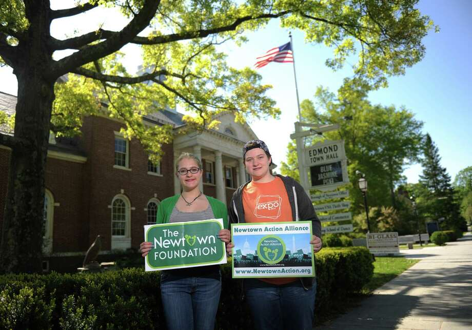 Newtown middle-schooler Tallie Nikitchyuk, left, and her sister, Ellie Nikitchyuk, a sophomore at Newtown High School, pose outside of Edmond Town Hall along Main Street in Newtown, Conn. Tuesday, May 20, 2014.  The sisters are going to participate in a summit this weekend for the Junior Newtown  Action Alliance, a gun violence-prevention group.  Tallie and Ellie's younger brother, Bear Nikitchyuk, was in Sandy Hook Elementary School the day of the shooting, but was fortunate to escape unharmed. Photo: Tyler Sizemore / The News-Times