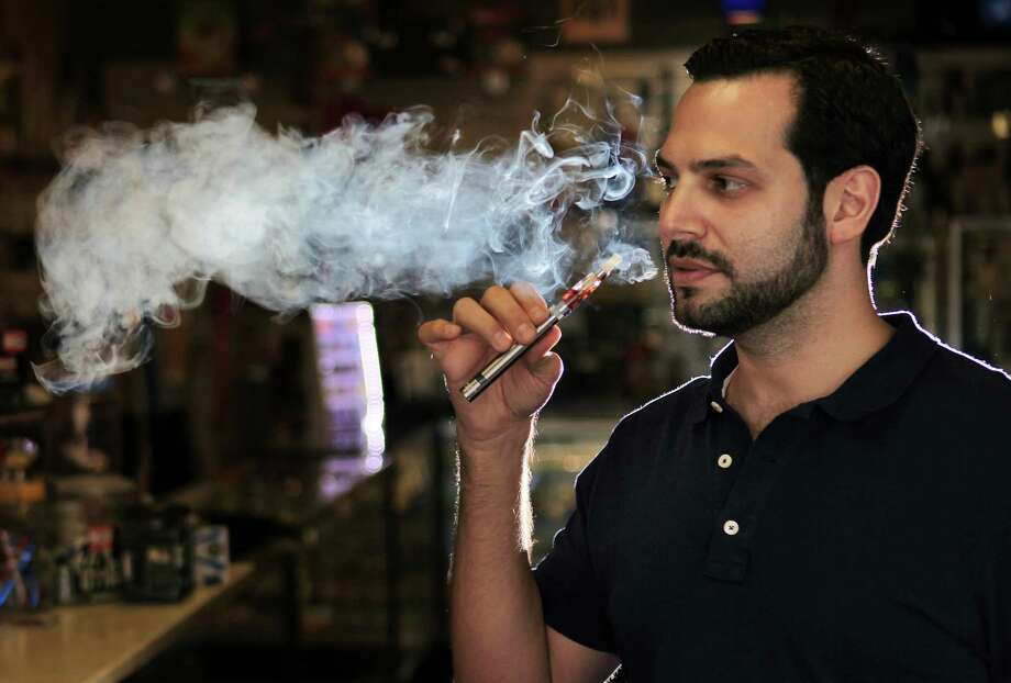 Jason Hanna, manager of Smoke Dreamz on Richmond, demonstrates one of the e-cigarettes sold at the store. Photo: Mayra Beltran, Staff / © 2014 Houston Chronicle