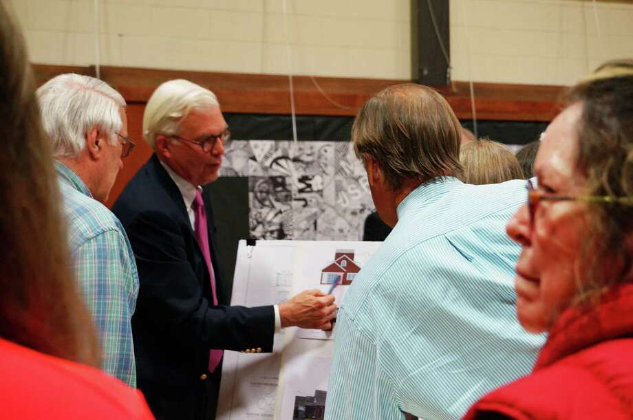 Architect John Franzen, in blue jacket, talks with  Greenfield Hill neighbors about proposed improvements to the Greenfield Mercato, prior to a Town Plan and Zoning hearing Tuesday. Photo: Genevieve Reilly / Fairfield Citizen