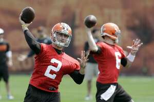 Johnny Manziel (2) throws with starter Brian Hoyer (6) in the background during a practice at the Browns' facility in Berea, Ohio on Wednesday.