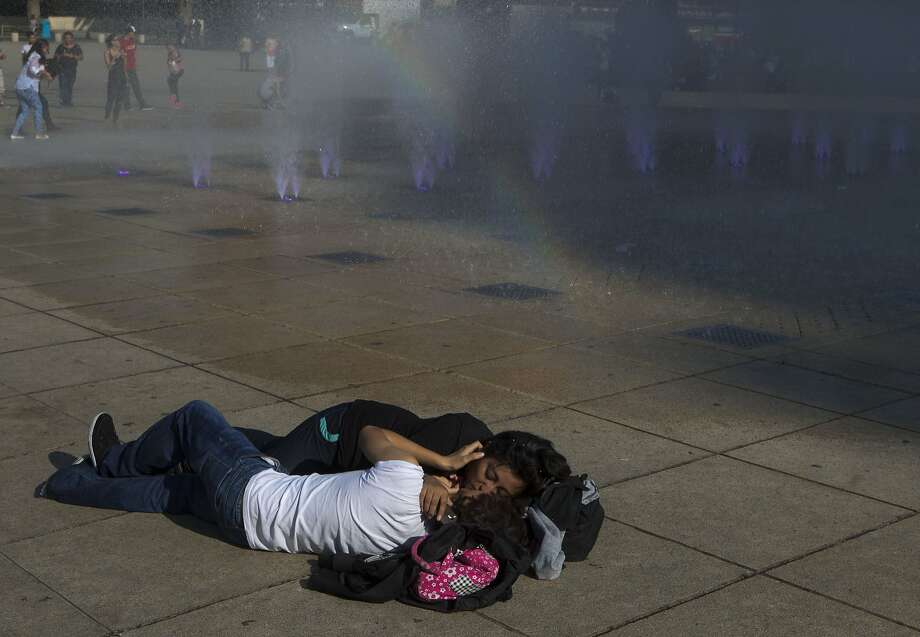 Cold shower's not working: A couple engage in an enthusiastic public display of affection by a fountain in Mexico City. Photo: Rebecca Blackwell, Associated Press