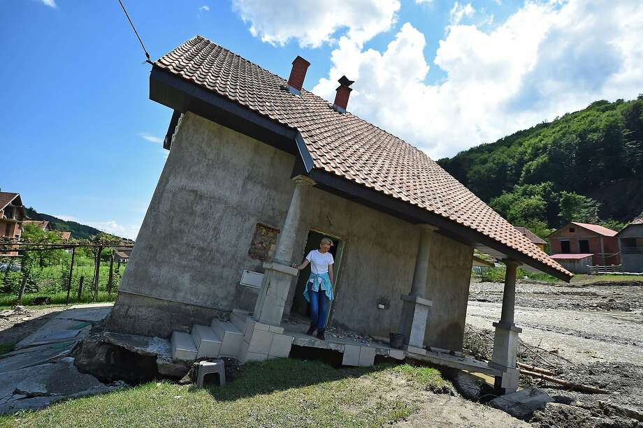 Listing house:Pavlovic Oksana stands on the front porch of her house, now tilting precariously after flooding in Krupanj, Serbia. The town was cut off for four days by high water and landslides. At least 49 people have been killed in the Central European floods. Photo: Andrej Isakovic, AFP/Getty Images