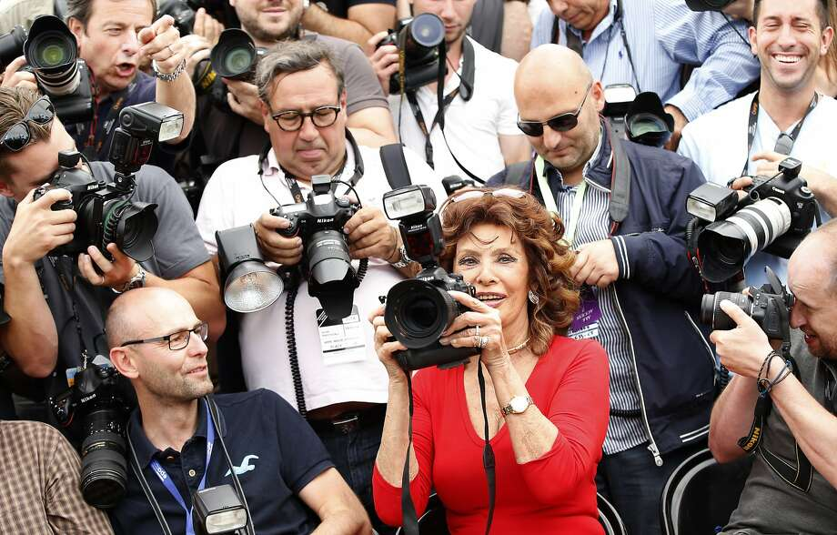 "Hey, lady, give me back my camera:Actress Sophia Loren, still glamorous as ever, snaps a few shots as she sits with photographers during a photo call for ""Human Voice,"" directed by her son, at Cannes. Photo: Alastair Grant, Associated Press"