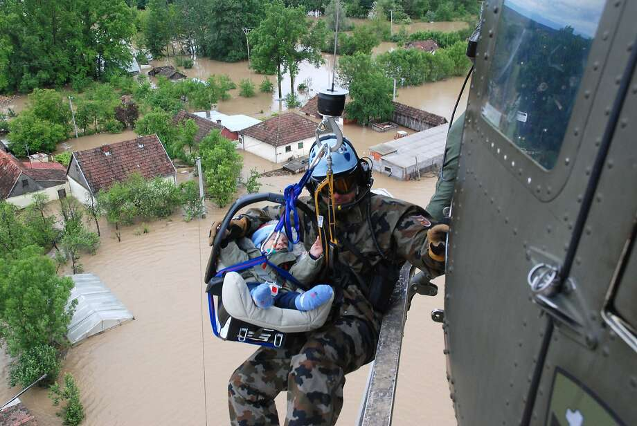 Bringing up baby: A Slovenian army helicopter team rescues an infant by winching the baby carrier to the chopper over the flooded village of Tisina in Bosnia-Herzegovina. The rest of the child's family was evacuated later. Serbia is suffering its worst flooding since it begin recording water levels 120 years ago. Photo: Rok Einhauer, Associated Press