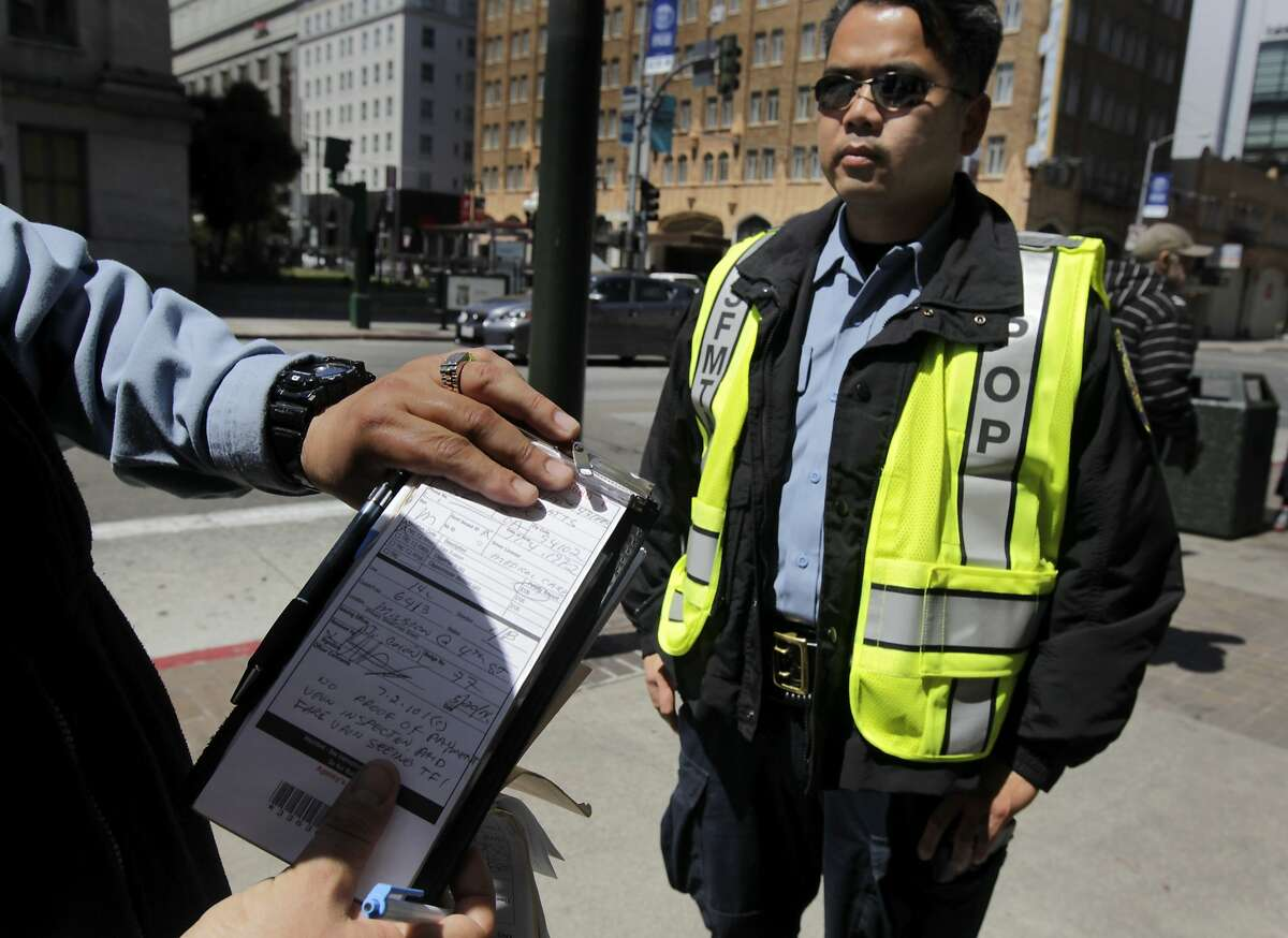 Muni transit fare inspectors J. Colon finishes writing up a citation while E. Doan (right) waits to board another 14-Mission bus arriving at Fith and Mission streets to check for fare evaders in San Francisco, Calif. on Tuesday, May 20, 2014. Many of the Clipper card fare readers aboard the buses are inoperable so some riders think they can ride for free.