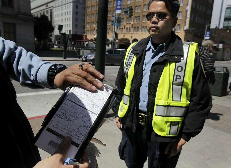 Muni fare inspector J. Colon finishes writing a citation while E. Doan (right) waits to board a 14- Mission bus at Fifth and Mission streets. Photo: Paul Chinn, The Chronicle