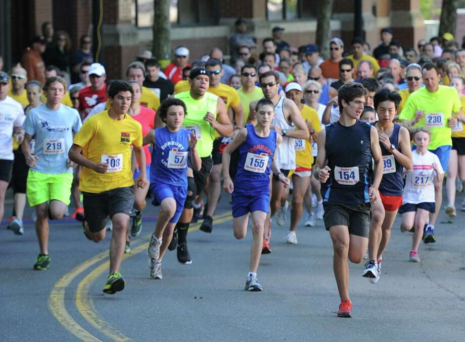 Runners take off from the starting line in the third annual Danbury Memorial Day 5K at CityCenter Green on Ives Street in Danbury, Conn. on Monday, May 27, 2013. The race returns for another year on Monday, May 26, 2014, launching a day full of holiday activities, including the Danbury Memorial Day parade. Photo: Tyler Sizemore / The News-Times