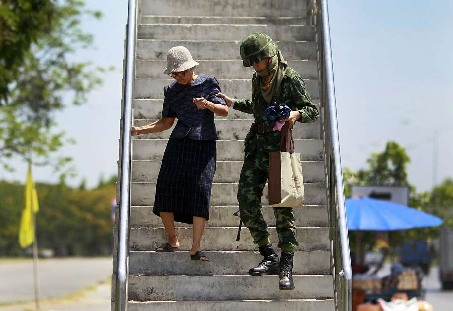 A soldier helps a woman down stairs near a pro-government demonstration site in Bangkok. Photo: Wason Wanichakorn, Associated Press