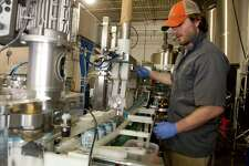 Tyler Wylie from Iron Heart Canning adjusts the speed of beer as he cans Bright Ale at Half Full Brewery in Stamford, Conn., on Wednesday, May 21, 2014.