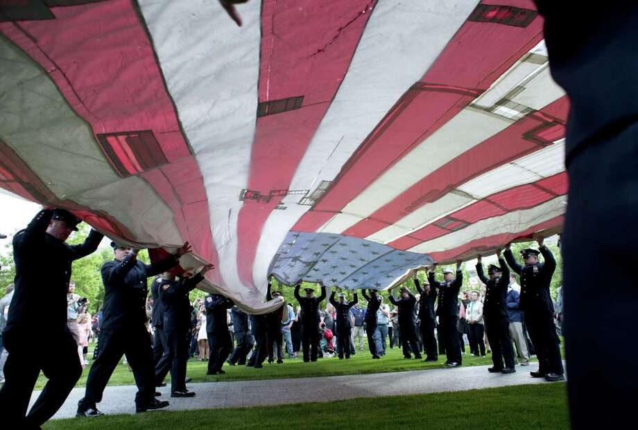 The National 9/11 Flag is furled by New York City firemen during a ceremony marking the opening  of the 9/11 Memorial Museum on May 21, 2014 in New York. After the ceremony the flag was transferred into the museum's permanent collection. Photo: DON EMMERT, AFP/Getty Images / AFP