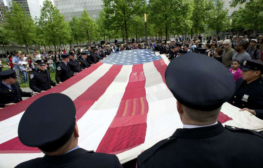 The National 9/11 Flag is held by New York City firemen during a ceremony marking the opening  of the 9/11 Memorial Museum on May 21, 2014 in New York. After the ceremony the flag was transferred into the museum's permanent collection. Photo: DON EMMERT, AFP/Getty Images / AFP