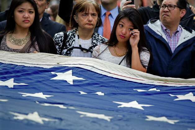 Genevive Amoncio, 17, of Levittown, N.Y., wipes a tear while standing by the National 9/11 Flag is at the 9/11 Memorial in New York Wednesday, May 21, 2014.  The ceremony Wednesday marked the opening of the National September 11 Memorial Museum. After the flag was refolded, firefighters marched it into the museum. The flag was flying from a building near the World Trade Center on Sept. 11, 2001. It was later found shredded in the debris of ground zero. Photo: Craig Ruttle, Associated Press / FR61802 AP