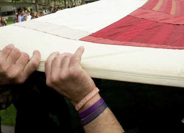 The hands of a fireman are seen as members of the public hold the National 9/11 Flag during a ceremony marking the open