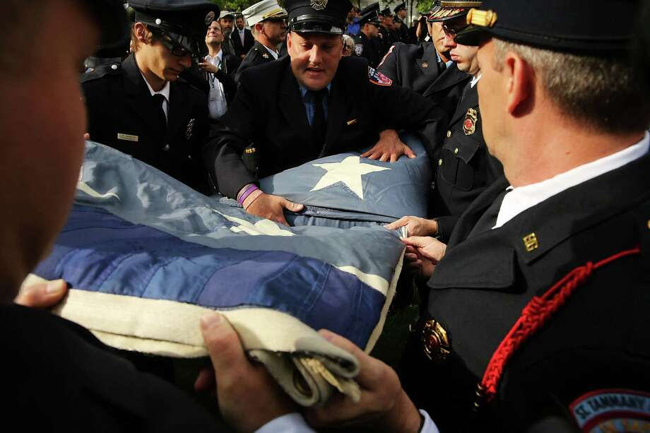 Firefighters help fold the flag as they participate in the ceremonial transfer of the National 9/11 Flag into the The National September 11 Memorial Museum permanent collection on May 21, 2014 in New York City. Photo: Spencer Platt, Getty Images / 2014 Getty Images