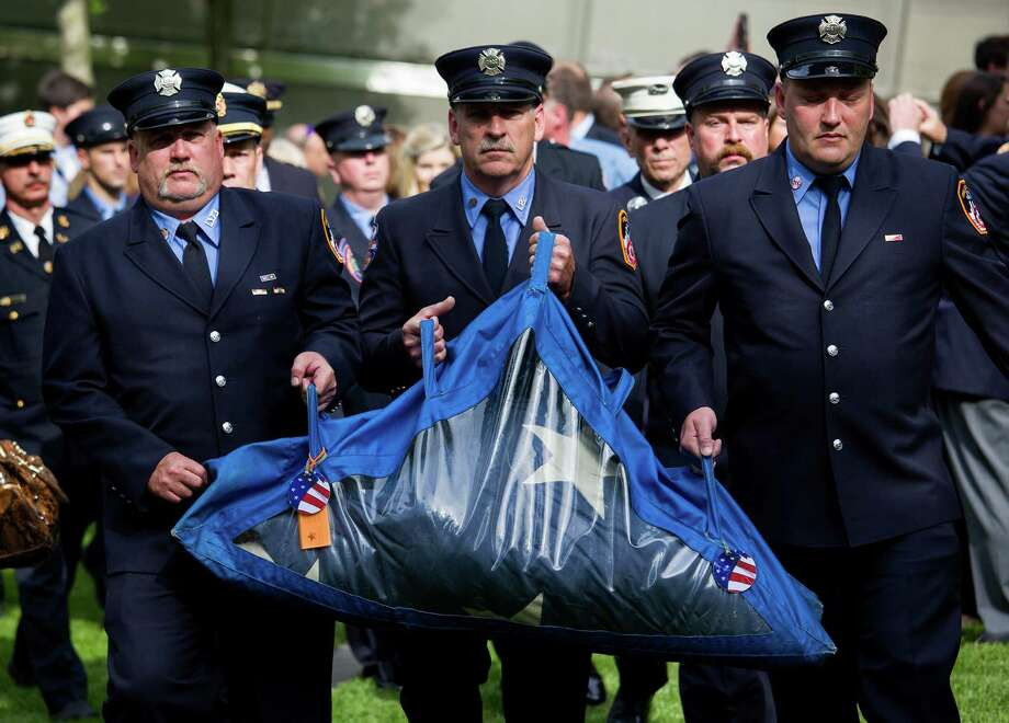 The National 9/11 Flag is carried by firefighters to the 9/11 Memorial Museum after a ceremony at the 9/11 Memorial in New York Wednesday, May 21, 2014.  The ceremony Wednesday marked the opening of the National September 11 Memorial Museum. After the flag was refolded, firefighters marched it into the museum. The flag was flying from a building near the World Trade Center on Sept. 11, 2001. It was later found shredded in the debris of ground zero. Photo: Craig Ruttle, Associated Press / FR61802 AP
