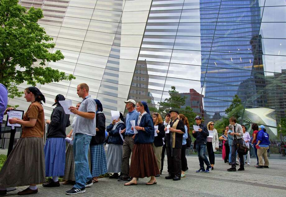 The reflective windows of the 9/11 Memorial Museum rise above some of the first public visitors to arrive at the site in New York Wednesday, May 21, 2014. Today marked the first day the 9/11 Memorial Museum was opened to the public. Photo: Craig Ruttle, Associated Press / FR61802 AP