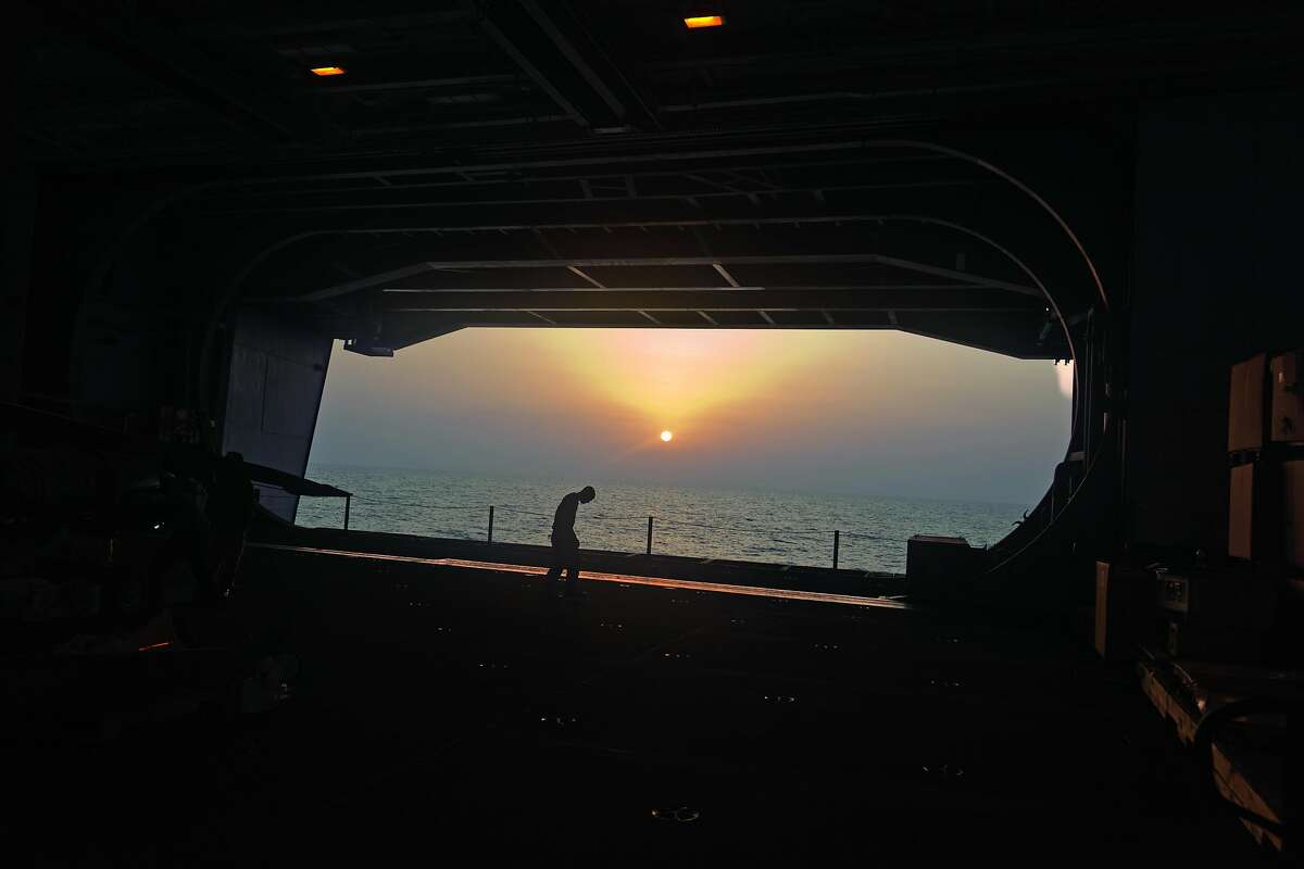 USA. American aircraft carrier USS George H W Bush. NImitz class. Nuclear powered with a crew of sailors and airmen of over 5,000. Somewhere in the Arabian Gulf. Inside the hanger at dusk.