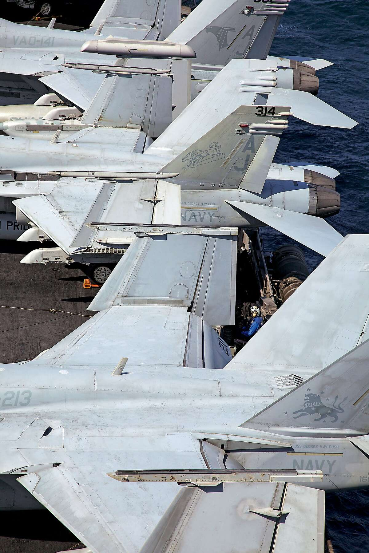 USA. American aircraft carrier USS George H W Bush. NImitz class. Nuclear powered with a crew of sailors and airmen of over 5,000. Somewhere in the Arabian Gulf. Jet fighters parked up on deck.