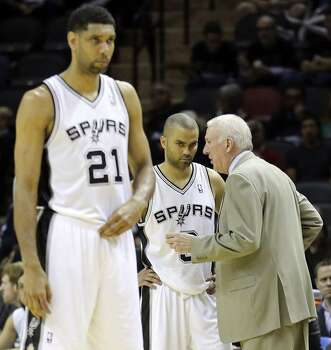 San Antonio Spurs' Tim Duncan pauses during a timeout as Tony Parker talks with head coach Gregg Popovich during second half action of Game 1 in the first  round of the Western Conference playoffs against the Dallas Mavericks Sunday April 20, 2014 at the AT&T Center. The Spurs won 90-85. Photo: Edward A. Ornelas, San Antonio Express-News