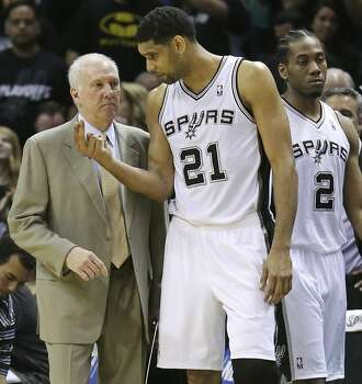 San Antonio Spurs head coach Gregg Popovich talks with Tim Duncan as Kawhi Leonard passes during first half action of Game 1 in the first round of the Western Conference playoffs against the Dallas Mavericks Sunday April 20, 2014 at the AT&T Center. Photo: Edward A. Ornelas, San Antonio Express-News