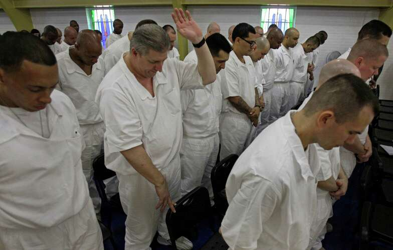 Prisoners at the Texas Department of Criminal Justice's Darrington Unit, 59 Darrington Unit Road, pray during a Convocation ceremony    Monday, Aug. 29, 2011, in Rosharon. Texas prison officials, Houston lawmakers and representatives of Southwestern Baptist Theological Seminary celebrated the opening of the state's first 4-year prison seminary program.   The nondenominational program, sponsored by the TDCJ, Southwestern Baptist Theological Seminary, Southern Baptists of Texas Convention and the Heart of Texas Foundation, will train inmates who are serving lengthy sentences to become ministers. Once they graduate from the program, the inmates will go to other Texas prison facilities where they will minister to their fellow offenders.  ( Melissa Phillip / Houston Chronicle )