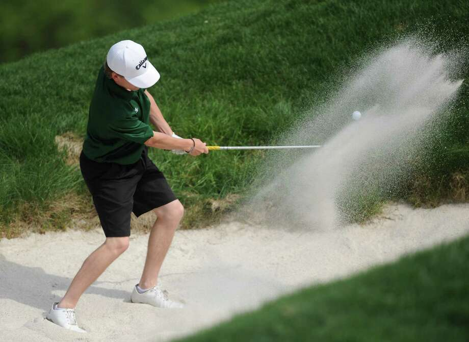 New Milford's Cole Case hits out of a bunker in the high school boys golf match between New Milford and Bethel at Redding Country Club in West Redding, Conn. Wednesday, May 21, 2014. Photo: Tyler Sizemore / The News-Times