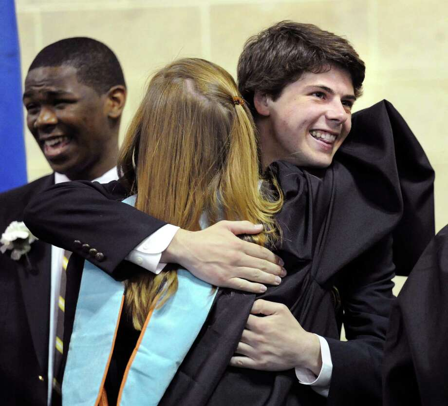 At right, Brunswick School graduating senior, Ian Coupe, 18, of Greenwich, gets a hug during the graduation ceremony at the school in Greenwich, Conn., Wednesday, May 21, 2014. Coupe said he will be attending Bucknell University in Lewisburg, Pennsylvania. Photo: Bob Luckey / Greenwich Time