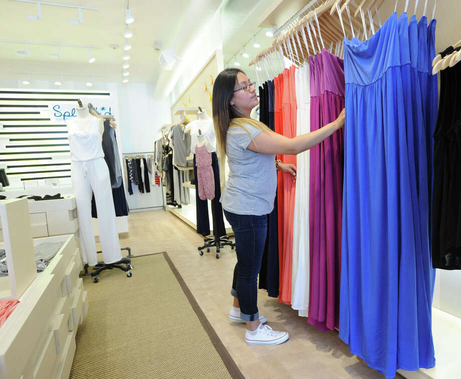 Rachel Rivas, an assistant manager at Splendid, arranges summer dresses at the store at 343 Greenwich Ave., Greenwich, Conn., Wednesday, May 21, 2014. The boutique specializes in casual branded apparel. Photo: Bob Luckey / Greenwich Time