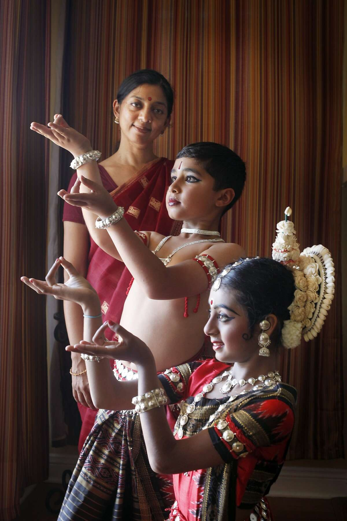 Teacher Niharika Mohanty, left poses with dancers Akhil Srinivasan Joondeph and Maya Lochana Devalcheruvu, Wednesday May 14, 2014, in San Carlos, Calif. They are Indian dancers who performed at the first Ethnic Dance Festival.