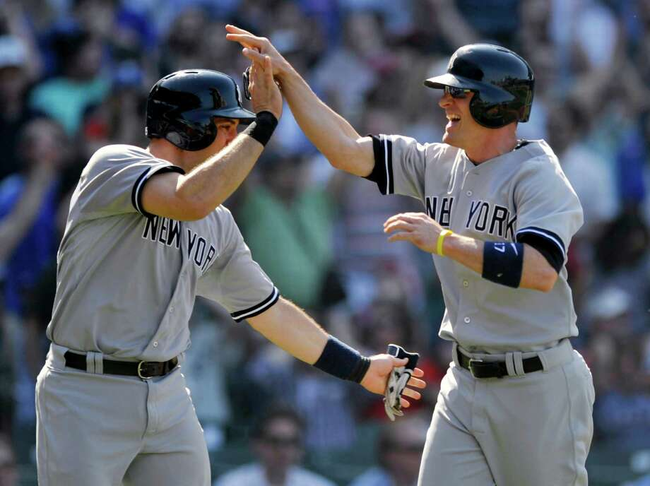 New York Yankees' Brendan Ryan right, celebrates with Mark Teixeria at home plate after both scored on a ball hit by Ichiro Suzuki during the ninth inning of an interleague baseball game against the Chicago Cubs in Chicago, Wednesday, May 21, 2014. (AP Photo/Paul Beaty) ORG XMIT: CXC107 Photo: PAUL BEATY / FR36811 AP