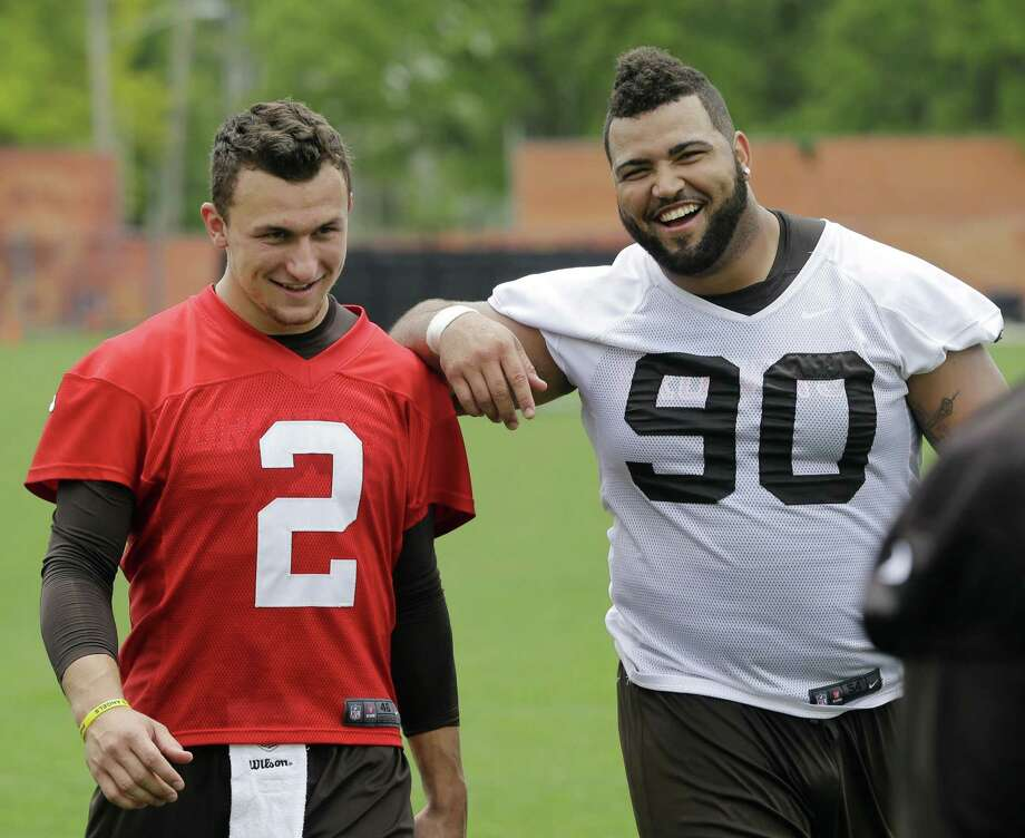 Cleveland Browns defensive end Billy Winn (right) shares a light moment with rookie quarterback Johnny Manziel at practice Wednesday. Photo: Mark Duncan / Associated Press / AP