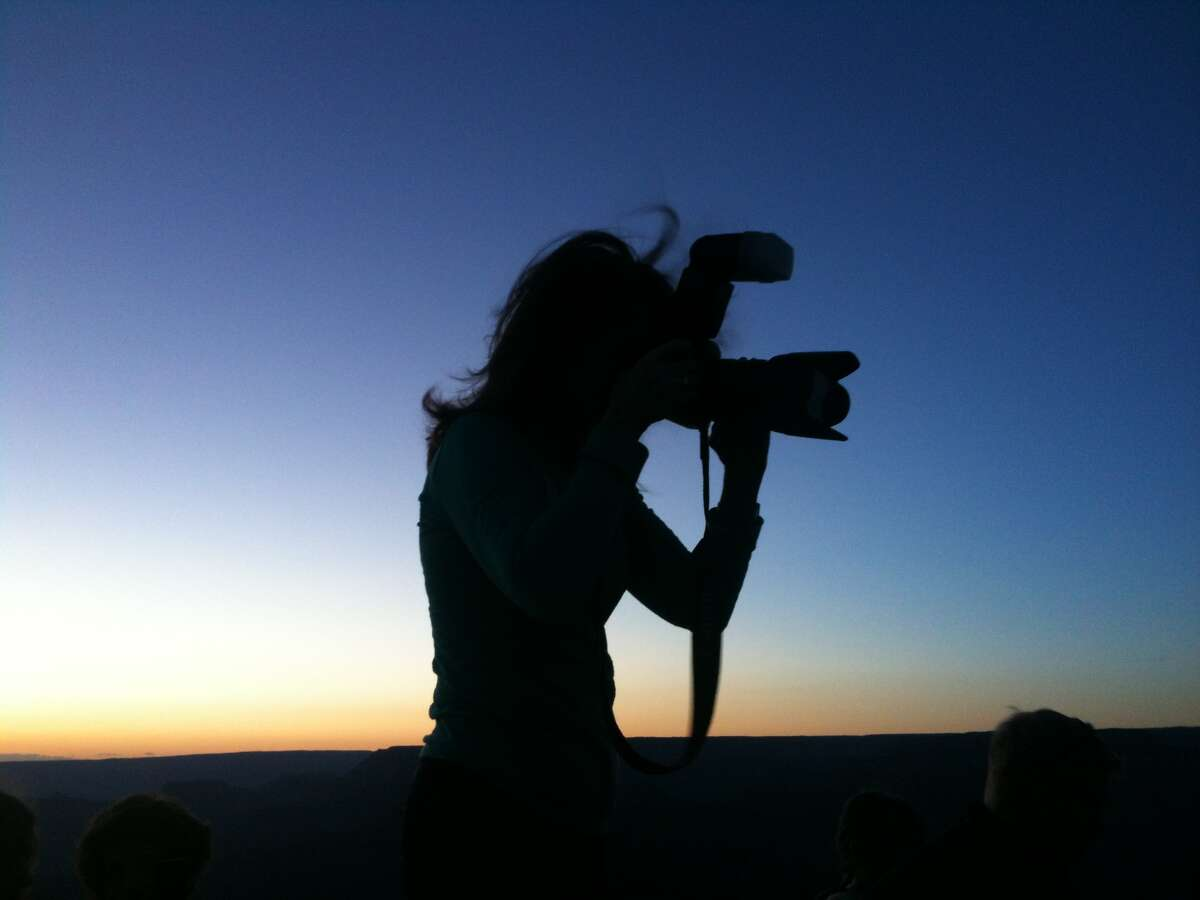 Photographer Judy Sanders is shown in silhouette as she captures the grandeur of the Grand Canyon at sunrise in a photo taken by her sister. (Photo courtesy Vicki Sanders)