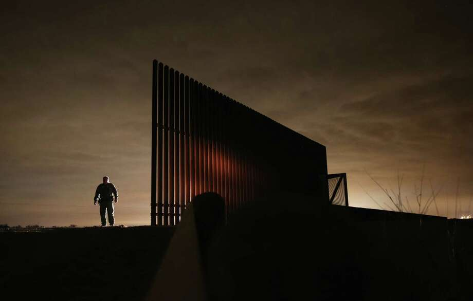 A Border Patrol agent stands near a section of border fence last year in La Joya. Lt. Gov. David Dewhurst wants a three-month border operation that would boost the number of troops, aircraft and boats to fight smuggling and drug cartel crimes. Photo: Getty Images File Photo / 2013 Getty Images