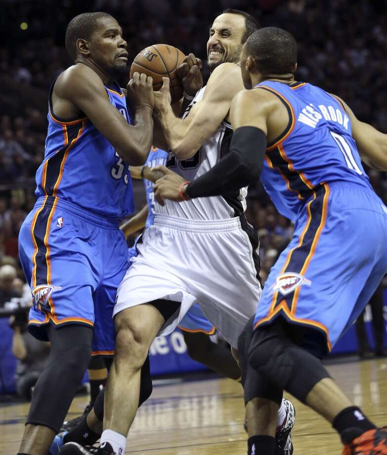 Manu Ginobili draws a foul on Kecin Durant as he squeezes into the lane against Russell Westbrook as the San Antonio Spurs play the Oklahoma City Thunder in game 2 of the Western Conference Finals at the AT&T Center on May 21, 2014. (Tom Reel/Express-News) Photo: TOM REEL