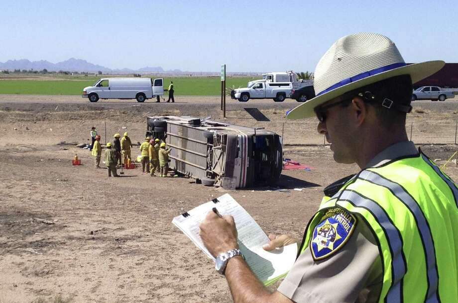 A Highway Patrol Officer goes over paperwork at a fatal bus crash in Blythe, Calif., where a tractor-trailer spilled a load of steel pipes onto a highway, triggering the crash. Photo: Brian Skoloff / Associated Press / AP
