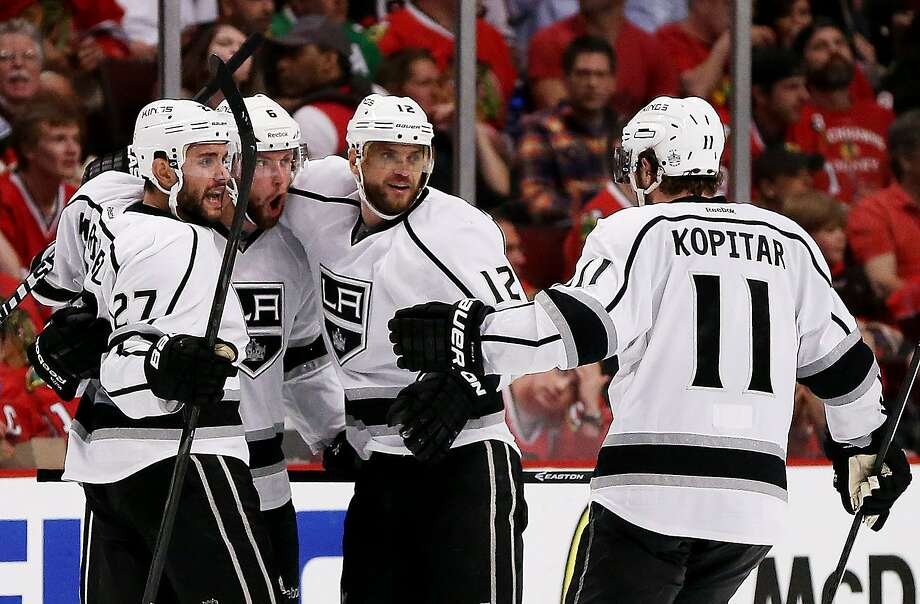 Teammates converge on Jake Muzzin (second from left) after his third-period goal gave the Kings the lead. Photo: Jonathan Daniel, Getty Images