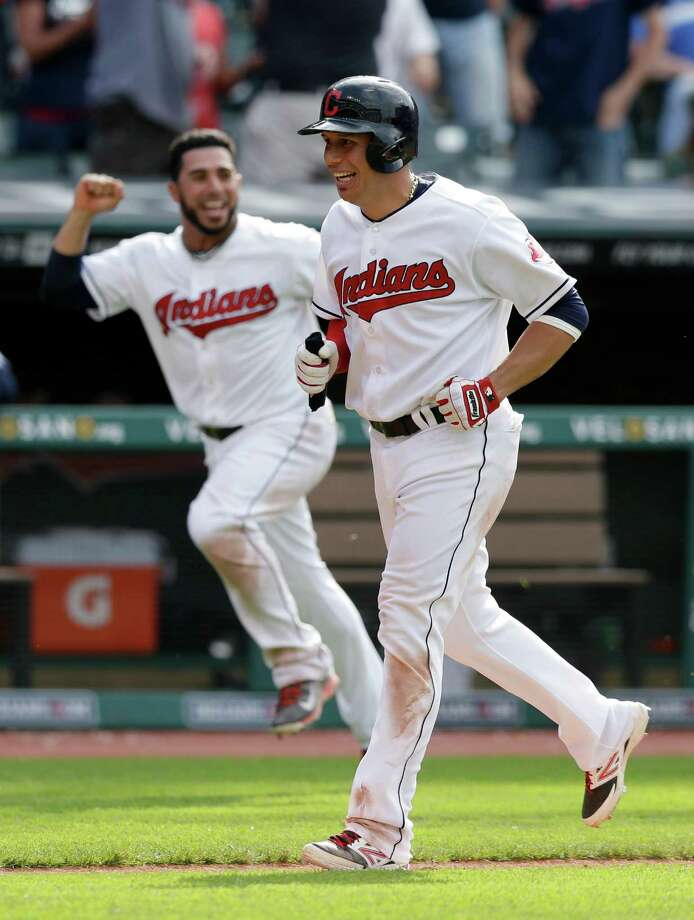 Cleveland Indians' Asdrubal Cabrera, right, runs to home plate before scoring the game-winning run after Detroit Tigers relief pitcher Al Alburquerque balked with the bases loaded in the 13th inning of a baseball game, Wednesday, May 21, 2014, in Cleveland. The Indians defeated the Tigers 11-10. (AP Photo/Tony Dejak) ORG XMIT: OHTD117 Photo: Tony Dejak / AP