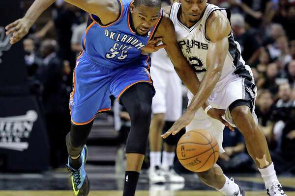 Oklahoma City Thunder's Kevin Durant and San Antonio Spurs' Kawhi Leonard chase after a loose ball during second half action of Game 2 in the Western Conference Finals Wednesday May 21, 2014 at the AT&T Center. The Spurs won 112-77.