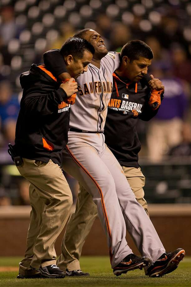 DENVER, CO - MAY 21: Relief pitcher Santiago Casilla #46 of the San Francisco Giants is helped off the field after tripping over first base and injuring himself while running the bases during the ninth inning against the Colorado Rockies at Coors Field on May 21, 2014 in Denver, Colorado. The Giants defeated the Rockies 5-1. (Photo by Justin Edmonds/Getty Images) Photo: Justin Edmonds, Getty Images