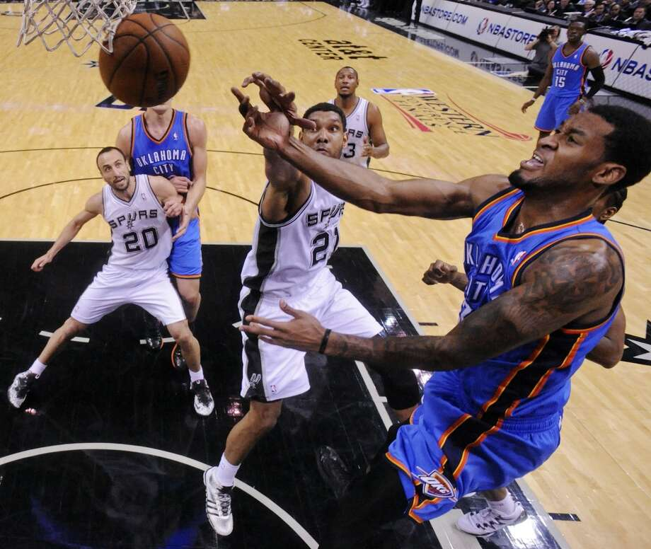 San Antonio Spurs' Tim Duncan and Oklahoma City Thunder's Perry Jones grab for a loose ball during first half action of Game 2 in the Western Conference Finals Wednesday May 21, 2014 at the AT&T Center. (Edward A. Ornelas/Express-News) Photo: Edward A. Ornelas, San Antonio Express-News