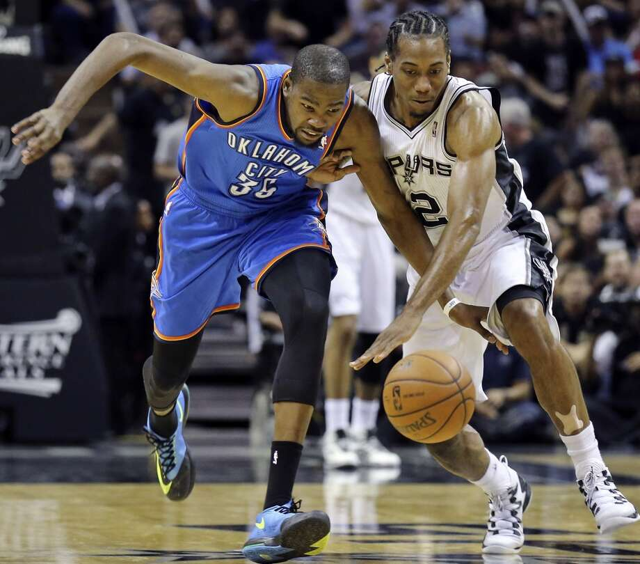 Oklahoma City Thunder's Kevin Durant and San Antonio Spurs' Kawhi Leonard chase after a loose ball during second half action of Game 2 in the Western Conference Finals Wednesday May 21, 2014 at the AT&T Center. The Spurs won 112-77. (Edward A. Ornelas/Express-News) Photo: Edward A. Ornelas, San Antonio Express-News